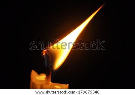 Close Up Candle With Creative Flame Over Dark Background (Noise Visible Due To Low Light Condition)