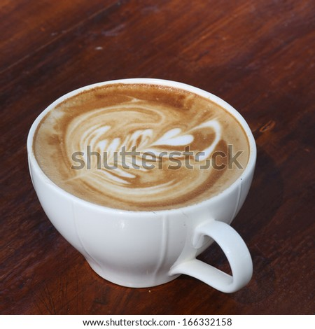 Close up cappuccino coffee on table with leaf face  - stock photo