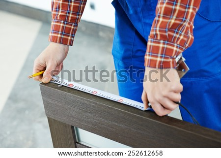Close-up carpenter hands with measure tape during process of wood door installation  - stock photo