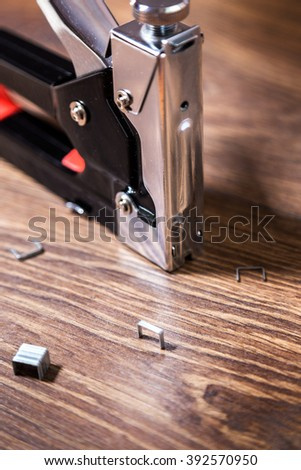 Close up carpentry stapler with staples on wood background - stock photo