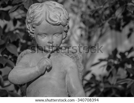 close up cement cherub doll in garden. Aged monochrome photo. Black and white. - stock photo