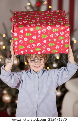 Close up Charming Young White Boy Carrying Big Christmas Box on his Head. Captured with Lighted Christmas Tree at the Background. - stock photo
