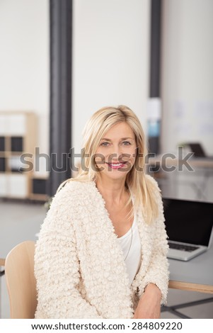 Close up Cheerful Adult Blond Office Woman Sitting on a Chair While Leaning Against her Desk and Looking at the Camera. - stock photo