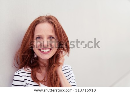 Close up Cheerful Blond Young Woman Leaning Against the White Wall and Smiling at the Camera While Holding her Hair. - stock photo
