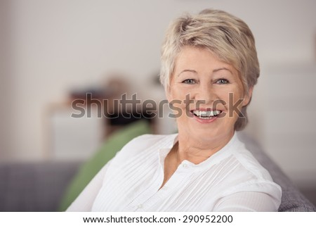 Close up Cheerful Portrait of a Middle Aged Blond Woman Looking at the Camera with a Toothy Smile.