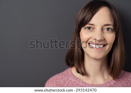 Close up Cheerful Pretty Adult Woman Against Plain Gray Wall Background, Looking at the Camera with Toothy Smile.