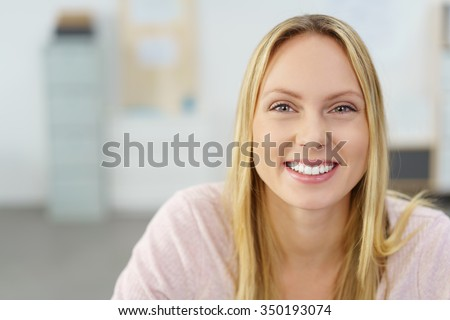Close up Cheerful Young Office Woman, with Long Blond Hair, Smiling at the Camera Against Blurred Workplace. - stock photo