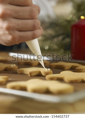 close up  chef decorating cookies with icing sugar