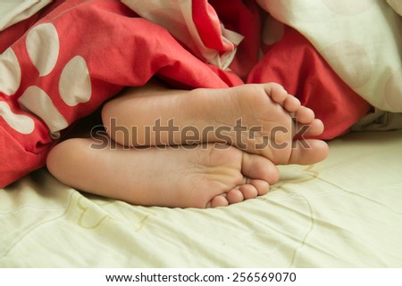 close up child feet in bed - stock photo