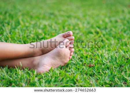Close up children feet on green grass in the park
