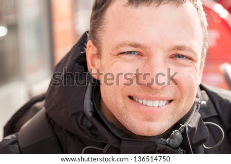Close up city outdoor portrait of young smiling man in cold season