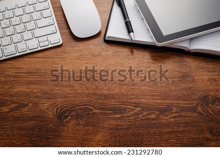 Close up Clean Open Notebook and Electronic Devices such as Keyboard, Mouse and Tablet, on Top of Wooden Table with Copy Space Below for Texts. - stock photo