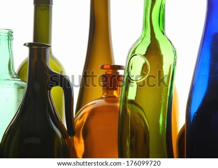close-up clean transparent colored glass bottles of different shapes on the mirror surface in white light studio