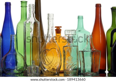 close-up clean transparent colored glass bottles of different shapes on the mirror surface in white light studio - stock photo