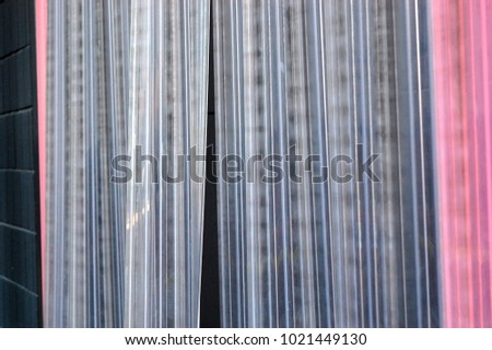 Close Up Clear Vinyl Plastic Lined Curtains And Black Painted Cinder Block Wall Behind Business