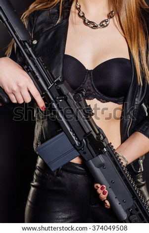Close-up cleavage woman in black with an sniper rifle in her hand - stock photo