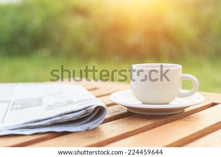 Close up Coffee cup and newspaper on the table in the morning - stock photo