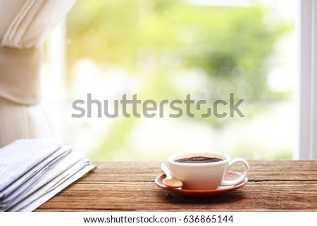Close up Coffee cup and newspaper on the table in the morning