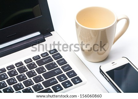Close up coffee cup with laptop and cell phone isolated on white background - stock photo