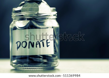 Close up Coins in glass jar for giving and donation concept , dark retro color tone