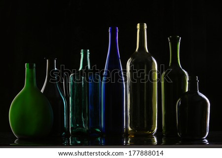 close-up collection of beautiful colored bottles of different shapes on a black background studio - stock photo
