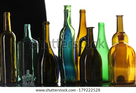close-up collection of beautiful colored bottles of different shapes studio on black and white background - stock photo