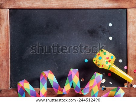 Close up Colored Festival Paper Streamer, Confetti and Whistle on Black Board. Emphasizing Copy Space. - stock photo
