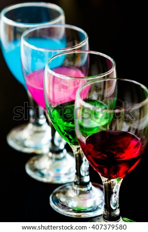 close up colorful cocktail into glass on black background - stock photo