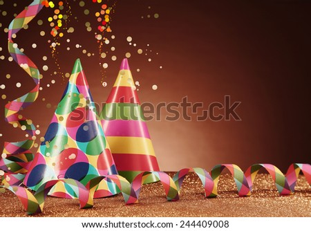 Close up Colorful Cone Party Hats and Paper Streamers on Table with Particles, Styled with Confetti Effect, on Gradient Brown Background. - stock photo