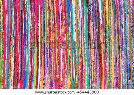 Close up colorful hand woven rug with red, blue, yellow, purple and other colors as background - stock photo