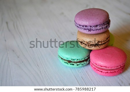 Close up colorful macarons dessert on a wooden table. Sweet french macaroons background.