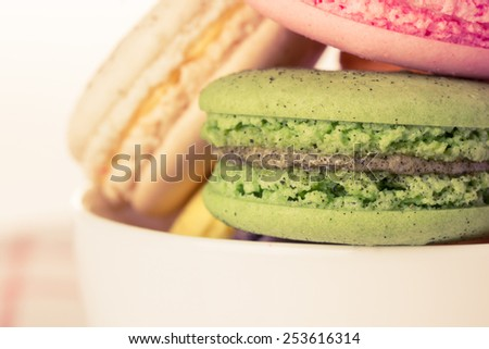 Close up colorful macaroons in the cup, vintage filter. - stock photo