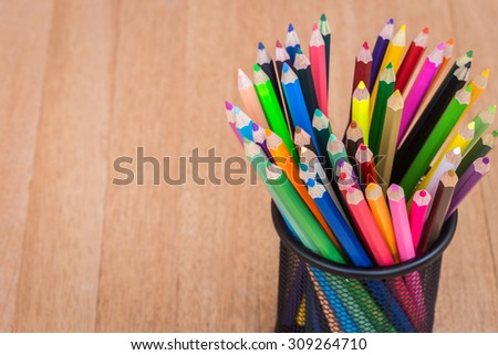 Close up colour pencils in steel bucket on wooden background