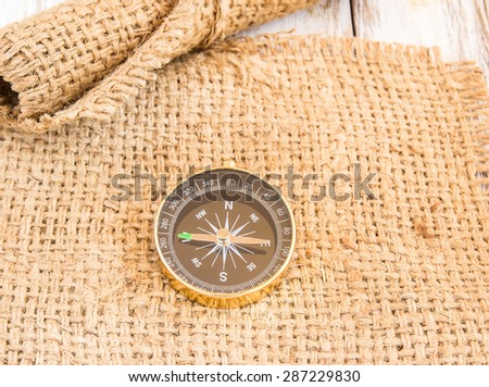 Close up compass on burlap sack on wooden background - stock photo