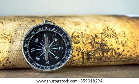 Close up compass on vintage map. Retro style.