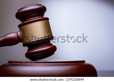 Close Up Conceptual Brown Wooden Gavel with Gold Plate Resting on the Table with Gradient Gray Brown Background.