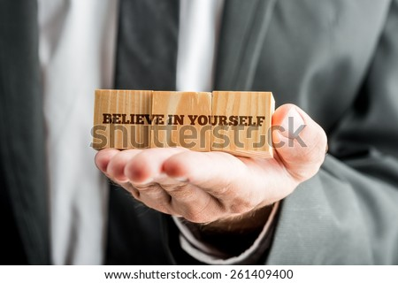 Close up Conceptual Businessman Showing Wooden Blocks with Believe in Yourself Message in Front of the Camera. - stock photo