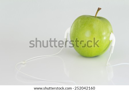 Close up Conceptual Fresh Green Apple with Headset Isolated on White. Emphasizing Copy Space.