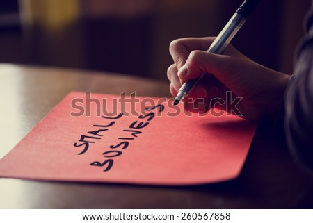 Close up Conceptual Man Writing Small Business Message on a Red Paper on Top of a Wooden Table, Toned Retro Effect. - stock photo