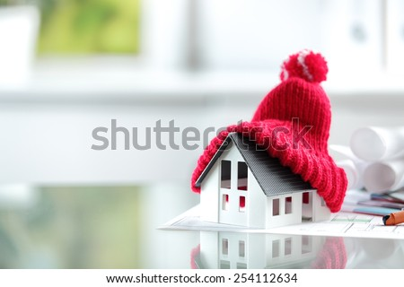 Close up Conceptual of Insulation Symbol House with Red Bonnet in office burreau. - stock photo