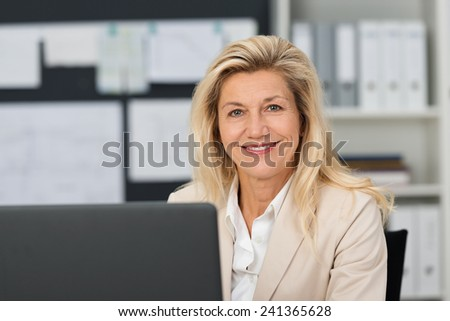 Close up Confident Adult Businesswoman, with Blond Hair, at her Office. Captured at her Working Table While Smiling at the Camera. - stock photo
