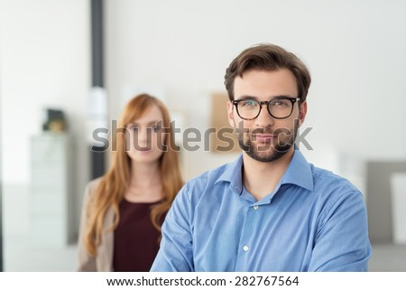 Close up Confident Bearded Young Businessman with Eyeglasses Smiling at the Camera While Standing In front of his Female Co-Worker Inside the Office. - stock photo