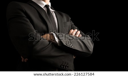 Close up Confident Businessman in Black Elegant Business Suit with Crossed Arms in Front of the Body. Isolated on Black Background. - stock photo