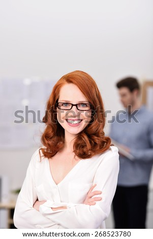 Close up Confident Young Businesswoman with Eyeglasses Smiling at the Camera while Crossing her Arms In Front her Body Inside the Office. - stock photo