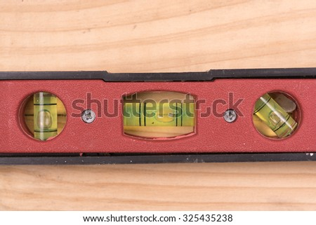 close up construction level ruler isolated on wooden background