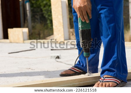Close up Construction Worker Use a Drill Device in Building a Real Estate House. - stock photo