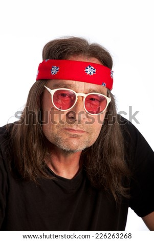 Close up Cool Older Long Hair Man Wearing Black Shirt, Sunglasses and Red Headband. Looking at Camera on White Background.