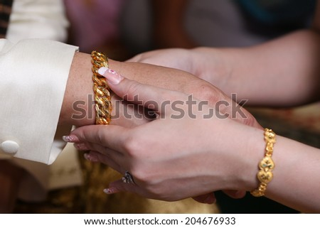 Close up couple putting gold chain for Engagement  in hotel