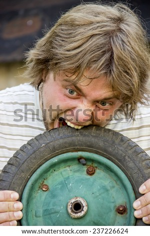 close-up crazy man eat the tire - stock photo