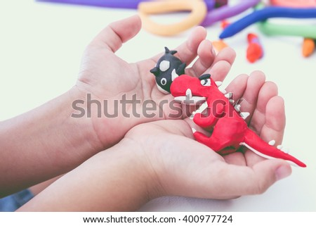 Close up. Creating red dinosaur and whale clay model, on white background. Animals from play dough on child hand. Education concept. - stock photo